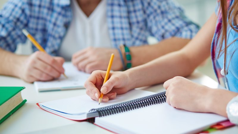 Hand of student with pencil carrying out written task or writing lecture